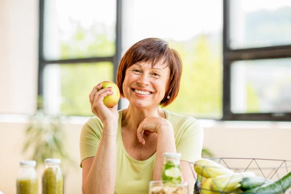 senior woman eating apple with permanent dental implants