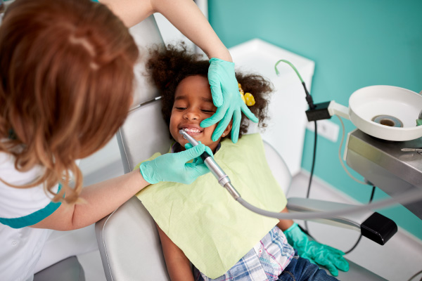 Young girl in the dental chair while female dentist uses a tool to examine and clean her teeth