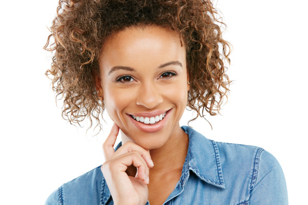 A young woman with curly brown hair smiles as she rests her hand on her face