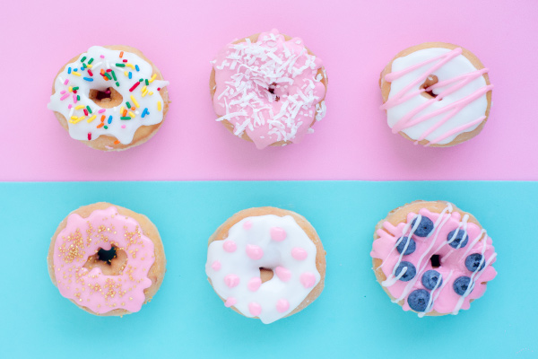 Aerial view of six donuts on a half pink, half blue counter with pink and white icing, sprinkles, and shredded coconut