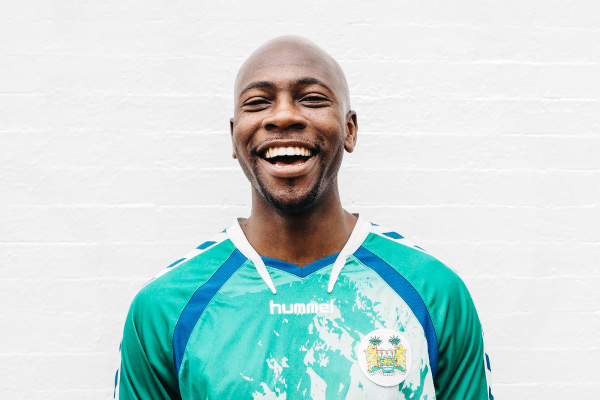 Bald man excited about xylitol wears a teal soccer jersey in front of a white brick wall and smiles with white teeth
