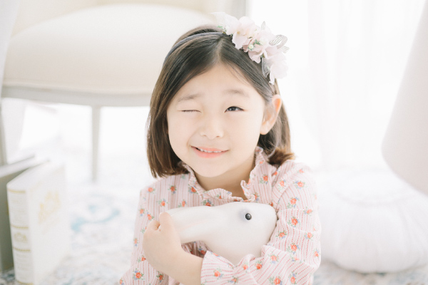 Dark-haired girl wearing a floral dress winks as she hugs a bunny stuffed animal to stay calm about visiting the dentist